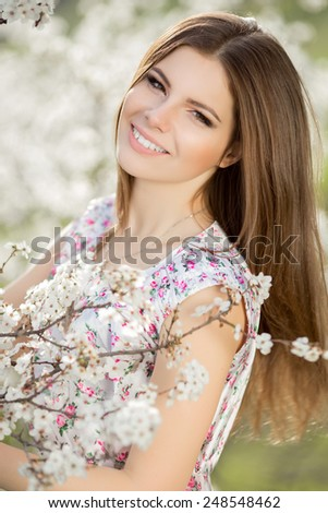 Beautiful woman spring portrait, smiling girl with flowers outdoor, beauty woman skin care, carefree young woman on nature, series.  - stock photo