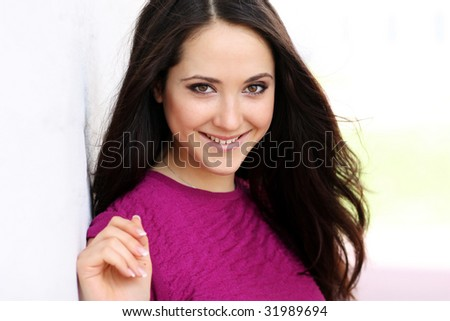Beautiful woman standing against wall in background