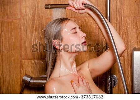 Beautiful woman standing at the shower.  She holds in her hand showerhead - stock photo