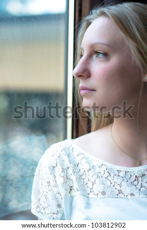 Beautiful woman standing by a window looking outside - stock photo