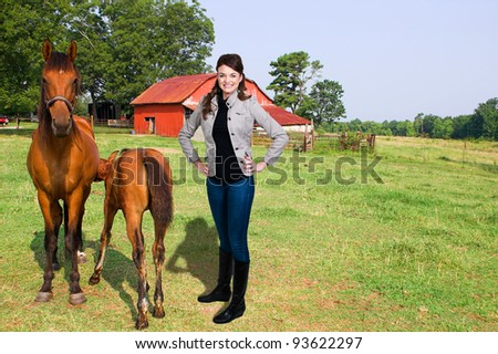 Beautiful woman standing next to foal having his breakfast in the early morning. - stock photo