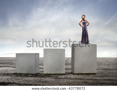 Beautiful woman standing on the highest of three cubes
