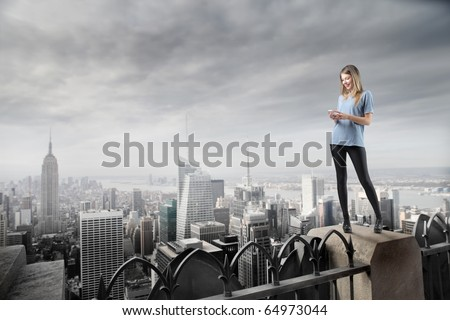 Beautiful woman standing on the top of a skyscraper and using a mobile phone - stock photo