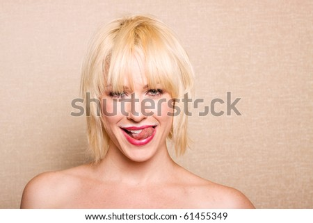 Beautiful woman sticking her tongue out after drinking milk - stock photo