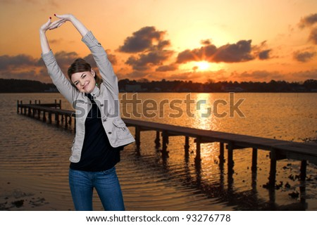 Beautiful woman stretching in a morning sunrise at the beach - stock photo