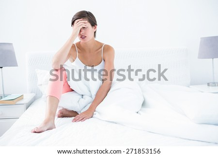 Beautiful woman suffering from headache at home in the bedroom - stock photo