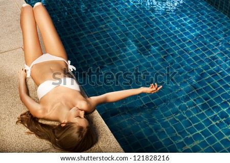 Beautiful woman sunbathing near swimming pool - stock photo