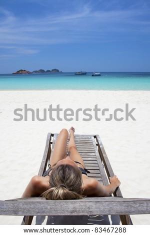Beautiful woman sunbathing on a beach chair in paradise, blue sky. - stock photo