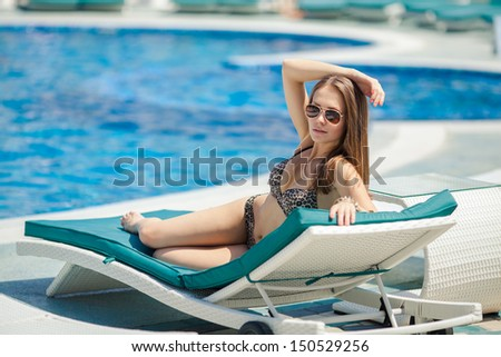 beautiful woman sunbathing on a tropical beach on a chaise lounge near swimming pool
