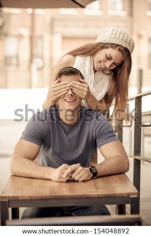 Beautiful Woman surprising her boyfriend at a street cafe - stock photo