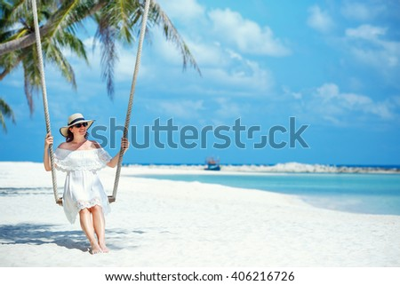 Beautiful woman swinging on a Tropical beach on Koh Phangan island. Thailand, Asia