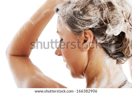 Beautiful woman taking a shower and shampooing her hair. Isolated on white. - stock photo