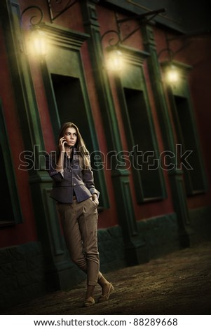 Beautiful woman talking on a cell phone in the night city - stock photo