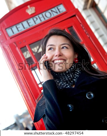 beautiful woman talking on the phone with a London phonebox behind her - stock photo