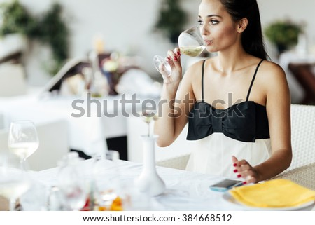 Beautiful woman tasting wine while sitting in restaurant - stock photo