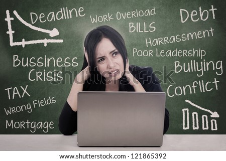 Beautiful woman teacher is sitting in front of her laptop and worry about lots of things - stock photo