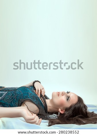 beautiful woman thinker lying on cyan background with copyspace - stock photo