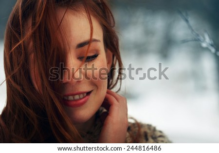 Beautiful woman thinking at her boyfriend while smiling and looking down. Winter background. - stock photo