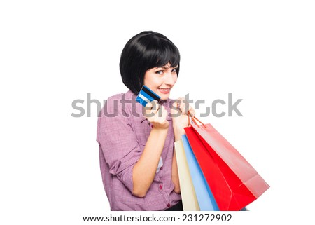beautiful woman thinking at something and holding credit card in hand with colored shopping bags - stock photo
