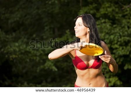 Beautiful woman throwing a Frisbee disc - stock photo