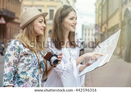 Beautiful woman tourists are looking for an address on the map on a old city street. One of them, blonde and wearing a hat. Other - brown hair, glasses on her head. They are smiling. Summer day.