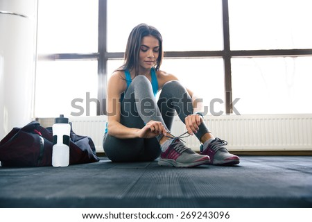 Beautiful woman tying shoelaces at gym  - stock photo