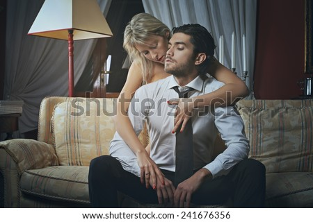 Beautiful woman undressing fashion elegant man. Love and celebration concept - stock photo
