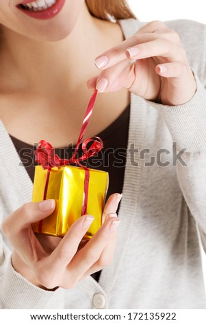 Beautiful woman unwrapping small present held in her hands. - stock photo