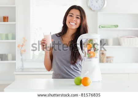 Beautiful woman using a blender while holding a drink in the kitchen