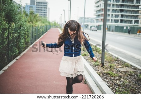 beautiful woman using smart phone and listening music in a desolate urban landscape - stock photo