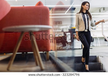 Beautiful woman using stairs in an office and smiling - stock photo