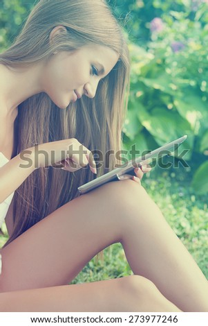 Beautiful Woman Using Tablet Computer In Garden, Park - stock photo