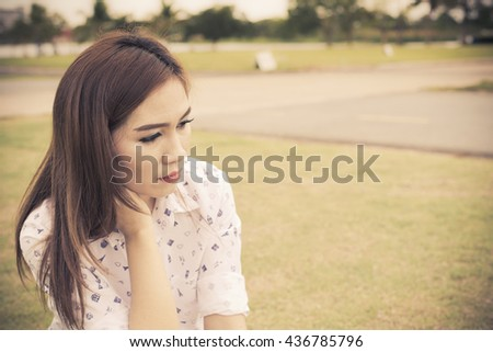 Beautiful woman very sad sit on grass alone she contemplate about love,vintage style - stock photo