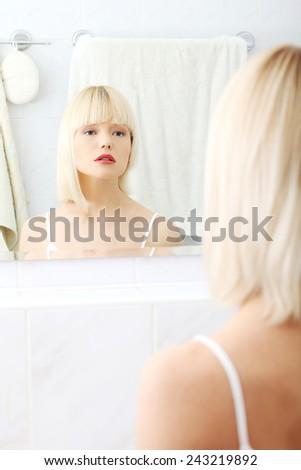 Beautiful woman viewing herself in the mirror. - stock photo