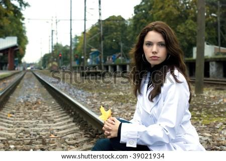 Beautiful woman waiting for the train on railway tracks - stock photo
