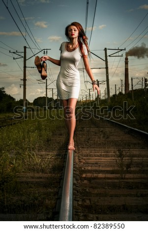 beautiful woman waiting for the train on railway tracks - stock photo