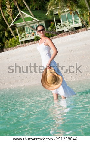 Beautiful woman walking along seaside on tropical beach