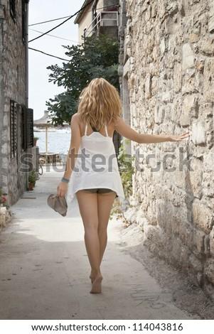 stock photo beautiful woman walking barefoot in the street by the sea croatia 114043816