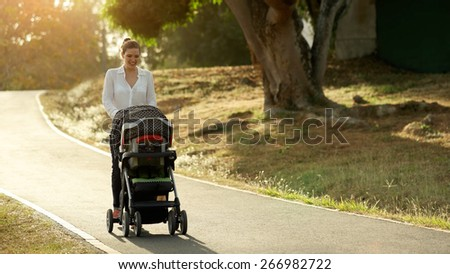 Beautiful woman walking down a lane in park with her little daughter and pushing pushchair, talking to her baby and smiling. Full length view at sunset - stock photo
