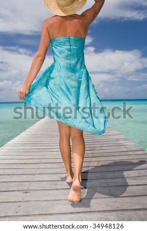 beautiful woman walking down pier in sarong - stock photo