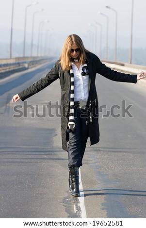 Beautiful woman walking on traffic line - stock photo