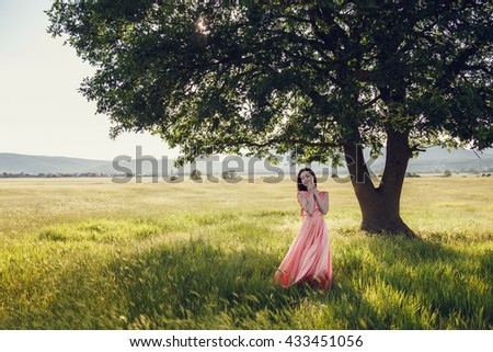 beautiful woman walking on wheat field before sunset. Cute lady walking through the meadow.