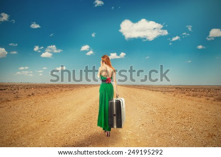 Beautiful woman walking through a desert road talking on mobile phone carrying big suitcase isolated on blue cloudy sky background. Embrace challenge unknown new life loneliness concept. Long journey  - stock photo