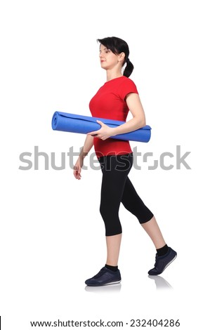Beautiful woman walking with mat for fitness - stock photo
