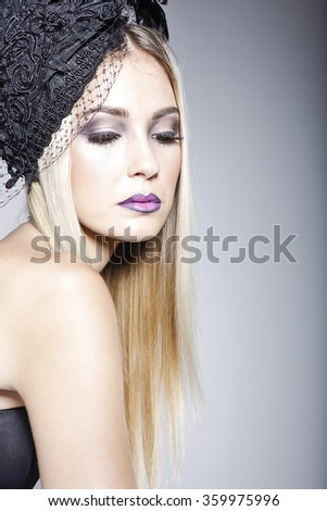 Beautiful woman wearing a black hat decorated with veil and a strapless top in a studio