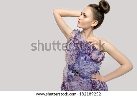 Beautiful woman wearing a purple dress with lace flowers and holding her hand on her hips. Girl posing fashion. Profile of a model - stock photo