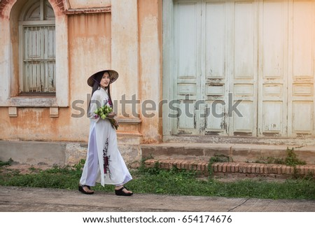 Beautiful woman wearing a Vietnamese dress Ao Dai holding lotus In abandoned buildings.