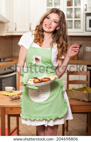 """Beautiful woman wearing an apron and serving someone with cookies; woman wearing a kitchen apron saying """"I have a skinny girl inside me screaming to get out but I shut her up with cupcakes"""" - stock photo"""
