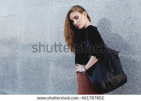 Beautiful woman wearing black blouse, brown pencil skirt and high heels shoes with leather bag posing at the evening city street. Vogue, female model