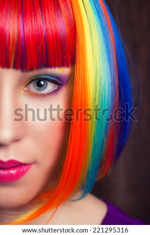 beautiful woman wearing colorful wig against wooden background - stock photo